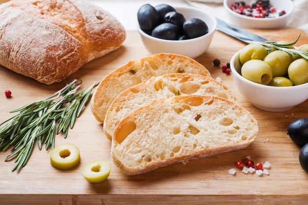 Italienisches ciabatta-brot mit oliven und rosmarin auf einem hölzernen brett
