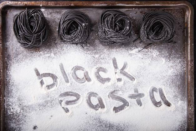Italienisches essen der ungekochten schwarzen teigwarenspaghettis