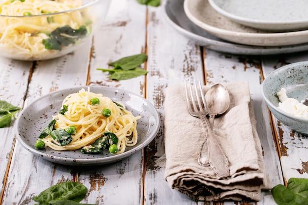 Italienisches essen: frische hausgemachte vegetarische tagliatelle-eiernudeln carbonara, serviert mit ricotta-käse und spinat über weißem holzhintergrund