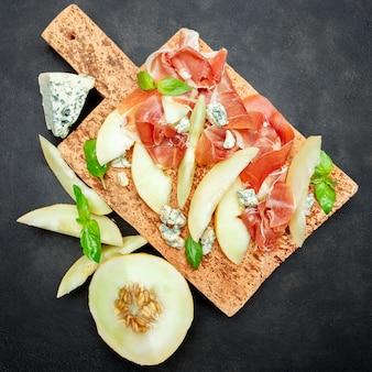 Italienisches essen mit melone, schinken und käse auf korkschneidebrett