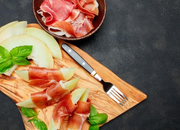 Italienisches essen mit melone und schinken auf holzschneidebrett