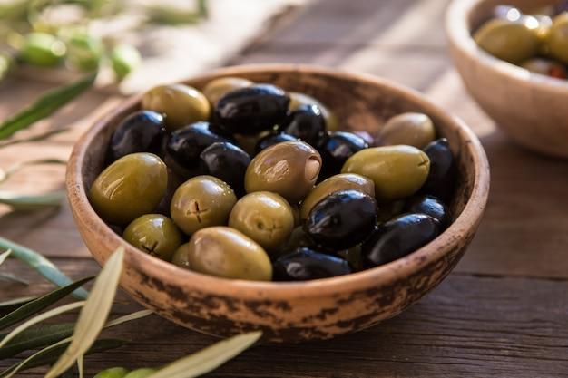 Italienisches essen, mit paprika und grünen oliven, gefüllt mit käse, schwarzen oliven, olivenöl auf holztisch