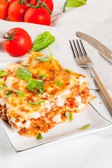 Italienisches essen rezept. abendessen mit klassischer lasagne bolognese mit bechamelsoße, parmesankäseparmesankäse, basilikum und tomaten, auf weißer marmortabelle, kopierraum