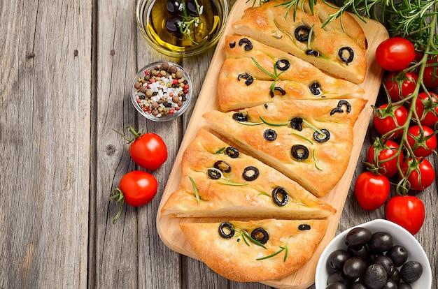 Italienisches focaccia-brot mit oliven und rosmarin auf rustikalem hölzernem hintergrund.