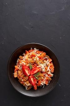 Italienisches gericht aus farbigen fusilli-nudeln in tomatensauce mit parmesan und gewürzen draufsicht