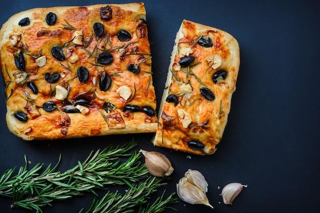 Italienisches hauptfocaccia mit oliven und rosmarin auf schwarzem hintergrund.