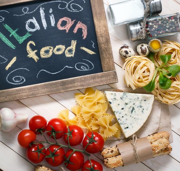 Italienisches lebensmittel auf hölzernem hintergrund der weinlese mit tafel