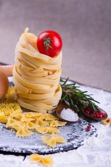 Italienisches lebensmittel - verschiedene teigwaren mit bestandteilen auf holztisch.