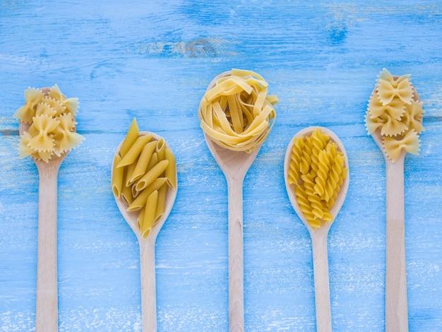 Italienisches lebensmittelkonzept und menüdesign. verschiedene arten von nudeln in holzlöffeln auf blauem holzhintergrund. flach liegen.