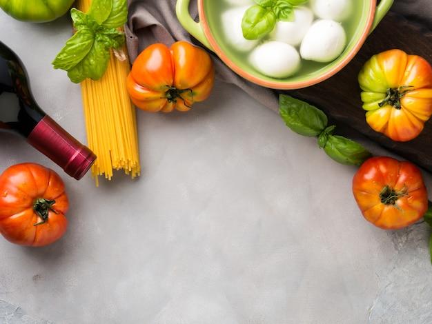 Italienisches lebensmitteltomaten-mozzarellastillleben auf grauem rustikalem hintergrund. traditionelle produkte