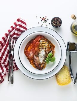Italienisches melanzane alla parmigiana gericht, hergestellt aus auberginen und tomaten auf einem tisch