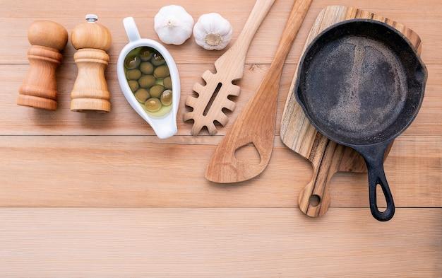 Italienisches nahrungsmittelkonzept und leere roheisenbratpfanne des menüs auf holztisch.
