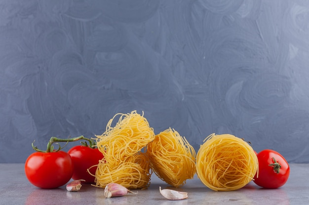 Italienisches nudel-fettuccine-nest mit frischen roten tomaten und gewürzen.