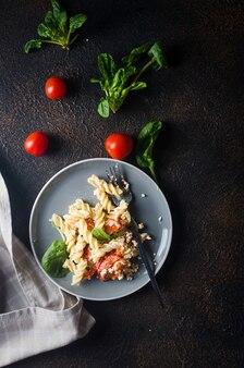 Italienisches nudelgericht, das mit gebackenem feta-käse und tomaten auf dunklem hintergrund mischt. fetapasta.
