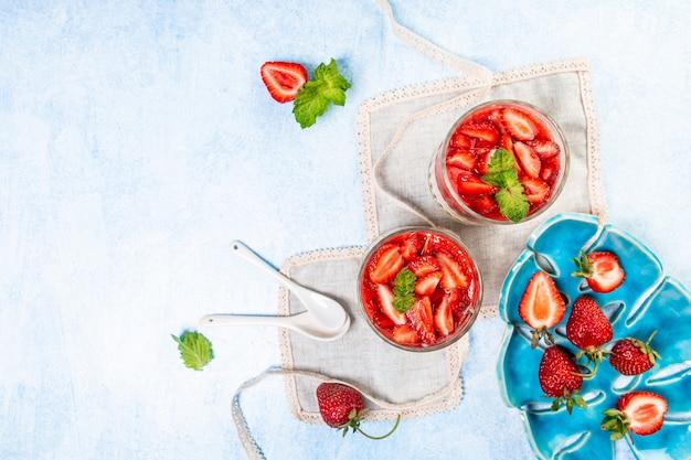 Italienisches panna cotta dessert mit erdbeermousse und minzblatt in transparenten gläsern