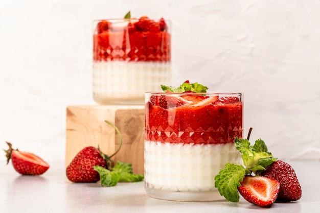 Italienisches panna cotta dessert mit erdbeermousse und minzblatt, serviert in kleinen transparenten gläsern