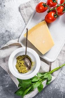 Italienisches pesto in marmormörser, basilikumblättern und parmesan auf einem schneidebrett. platz für text