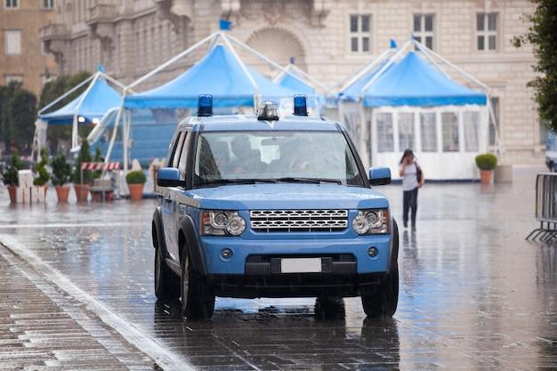 Italienisches polizeiauto unter dem regen