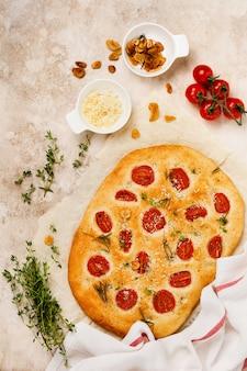 Italienisches traditionelles focaccia-brotbacken mit kirschtomaten, parmesan und rosmarin auf hellbraun