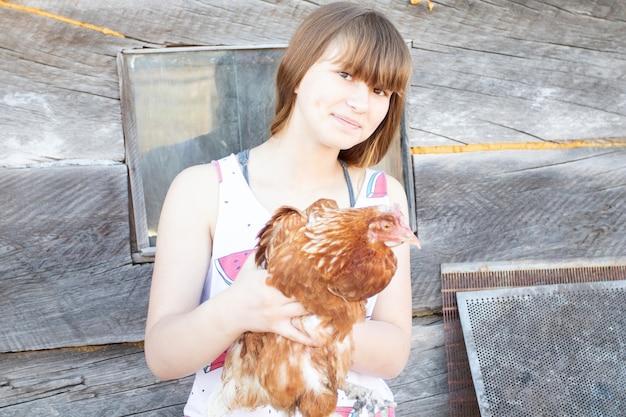 Ittle kindermädchen hält das chikem auf dem bauernhof.