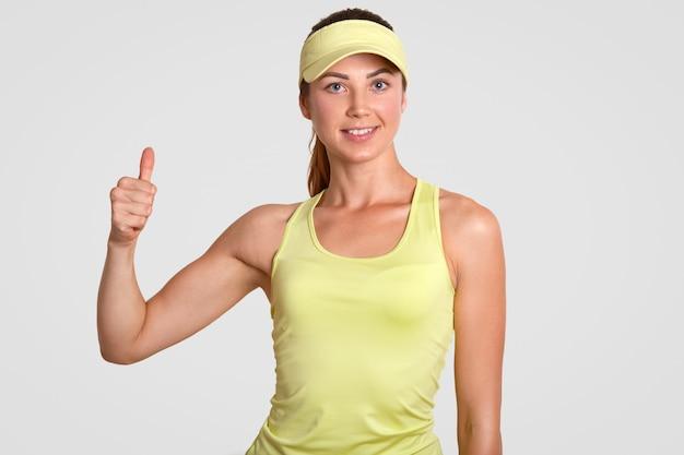 Ja, das war ein fantastisches spiel! glücklich entzückte aktive spielerin, tennisliebhaberin, macht eine gute geste, hält den daumen hoch und zeigt die ergebnisse des spiels, das über der weißen wand isoliert ist. körpersprachenkonzept