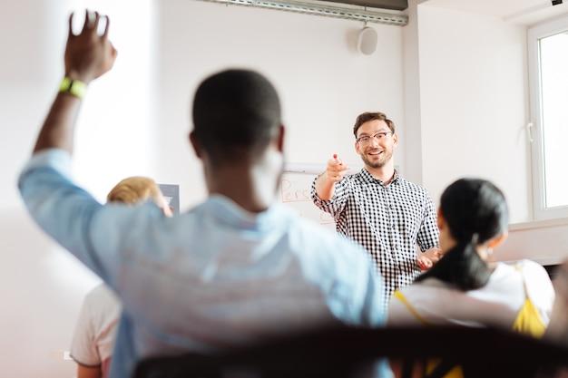 Ja du. fröhlicher freundlicher redner, der einen geschäftsworkshop leitet und auf einen studenten zeigt, der seine hand hebt
