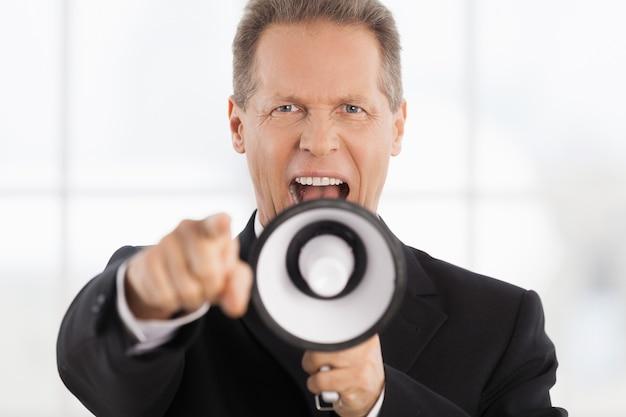 Ja du! porträt eines selbstbewussten reifen mannes in formeller kleidung, der am megaphon schreit und die kamera zeigt