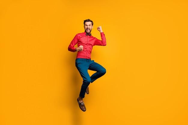 Ja! ganzkörperfoto von lustigen verrückten kerl springen hoch oben feiern lotterie geld gewinnen tragen trendige rote hemd fliege hosen schuhe outfit