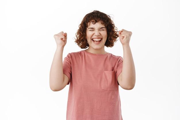 Ja gewinnen. aufgeregtes und triumphierendes kurviges mädchen, das den sieg feiert, sagt ja und jubelt, hebt die hände vor freude und sieg, erreicht den zielerfolg und steht auf weiß.
