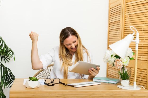 Ja. glückliche aufgeregte frau zu hause workstation triumphiert mit erhobenen händen