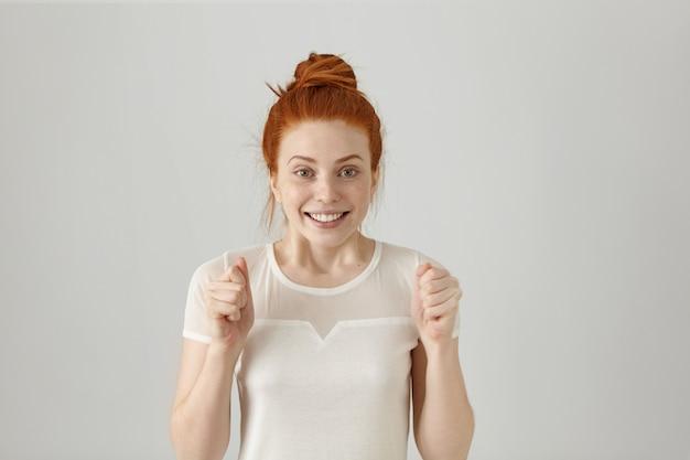 Ja! glücklicher erfolgreicher junger rothaariger frauensieger mit haarknoten, der die fäuste geballt hält, während er jubelt und sich glücklich fühlt, in aufregung und freude schaut und fröhlich lächelt