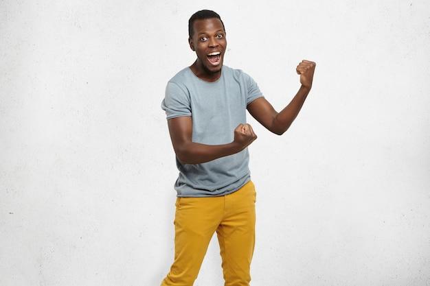 Ja! hübscher junger afroamerikanischer angestellter, der sich aufgeregt fühlt, aktiv gestikuliert, die fäuste geballt hält, freudig mit weit geöffnetem mund ausruft, glücklich mit viel glück oder beförderung bei der arbeit