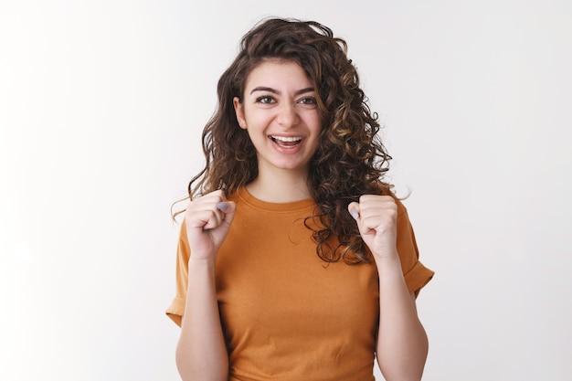 Ja, ich habe glück. fröhliche triumphierende junge fröhliche armenische frau mit lockigen fäusten, die erfolgreiche lottogewinne feiern, lächelnd, sagen ja, aufgeregtes gutes positives ergebnis, stehender weißer hintergrund
