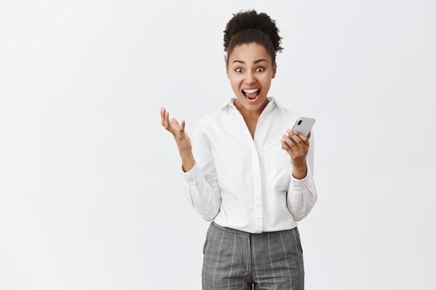 Ja mädchen, ich habe es getan. porträt der schockierten und überraschten glücklichen kreativen geschäftsfrau mit dunkler haut- und brötchenfrisur, gestikulierend, während sie smartphone hält, beeindruckende gute nachrichten über graue wand liest