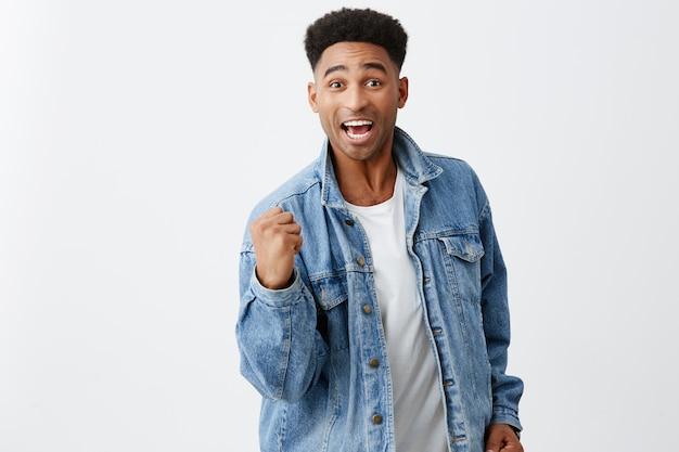 Ja. schließlich. wir haben es geschafft. fröhlicher junger attraktiver schwarzhäutiger mann mit afro-frisur in jeansjacke, der mit aufgeregtem ausdruck die hand vor sich hält und glücklich ist, dass er im lotto gewonnen hat.