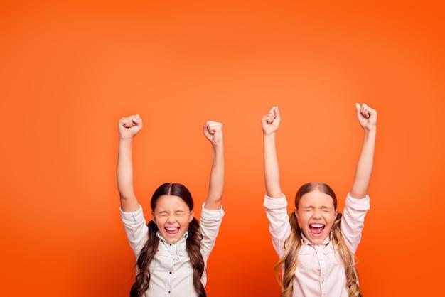 Ja unglaublicher sieg! porträt der glücklichen entzückten verrückten zwei kindermädchen gewinnen wettbewerb fühlen euphorie schreien erhöhen fäuste tragen moderne kleidung isoliert orange farbe hintergrund