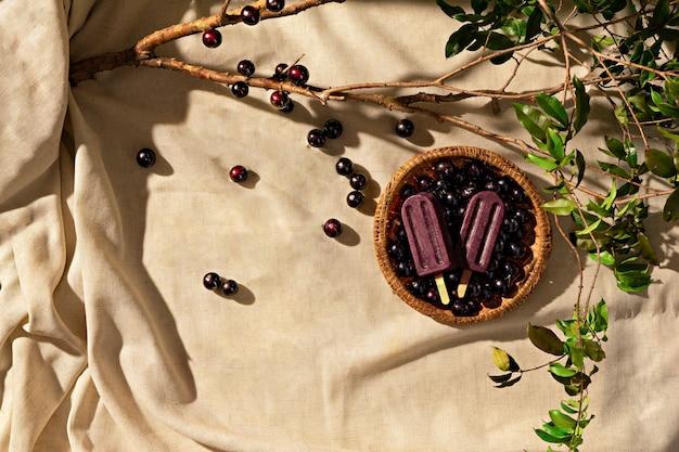 Jabuticaba-eis am stiel mit jabuticaba-früchten auf stoffunterlage, sonnenlicht, draufsicht
