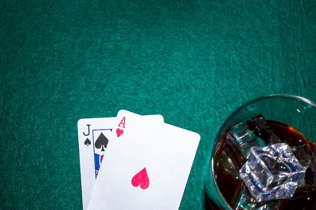 Jack der spaten- und herzass-spielkarte mit whiskyglas auf schürhakentabelle