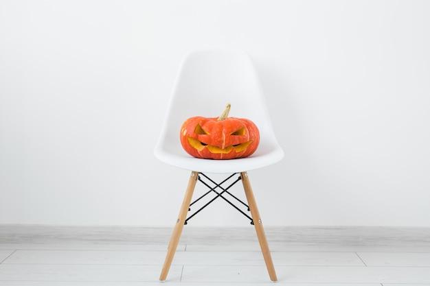 Jack-o-laterne geschnitzter kürbis auf einem weißen modernen stuhl auf heller wandwand, herbst- und halloween-wohnkultur.