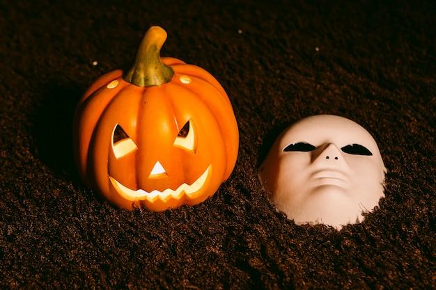 Jack-o-laterne kürbis mit licht im inneren zusammen mit einer weißen maske. halloween-konzept