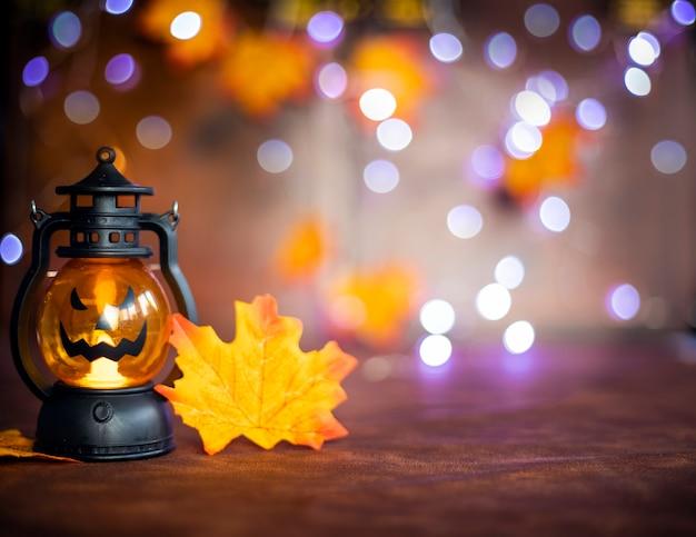 Jack o laternen halloween-kürbisgesicht im laternenherbst farbigen hintergrund mit bokeh-lichtern und herbstblättern