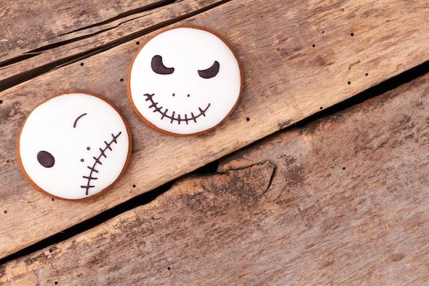 Jack skellington cookies auf holzuntergrund runde lebkuchen mit halloween-gesichter kopie s...