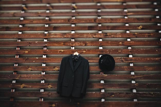 Jacke und bowler-hut hängt an einer holzwand