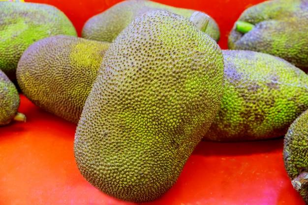 Jackfruitverkauf auf ganzer brotfrucht der straße auf einem hölzernen hintergrund