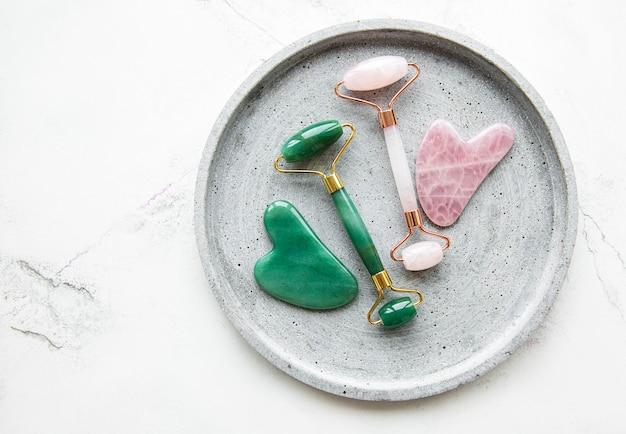 Jade-gesichtsrollen für die schönheits-gesichtsmassagetherapie. flach lag auf weißem marmorhintergrund