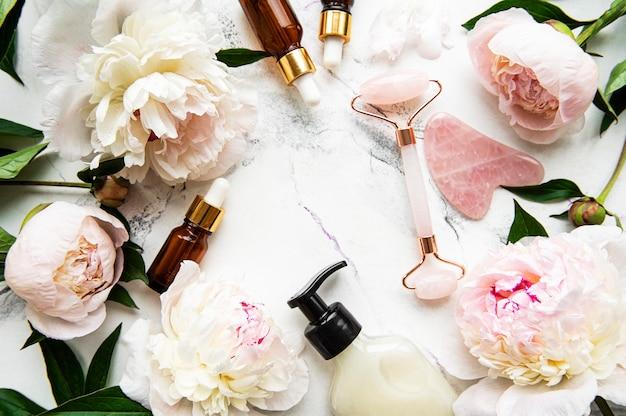 Jade-gesichtsroller für schönheits-gesichtsmassagetherapie, massageöle und rosa pfingstrosen. flach auf weißer marmoroberfläche liegen