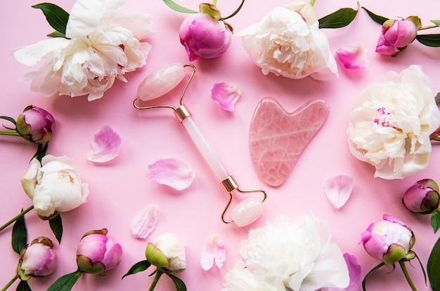 Jade-gesichtsroller für schönheits-gesichtsmassagetherapie und rosa pfingstrosen. flach lag auf rosa pastellhintergrund