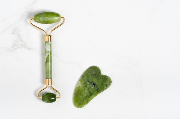 Jaderoller für die gesichtsmassage. grüne gua-sha-gesichtsmassagegeräte auf dem weißen marmorhintergrund mit kopienraum flach. anti-aging, lifting und toning behandlung, akupressur