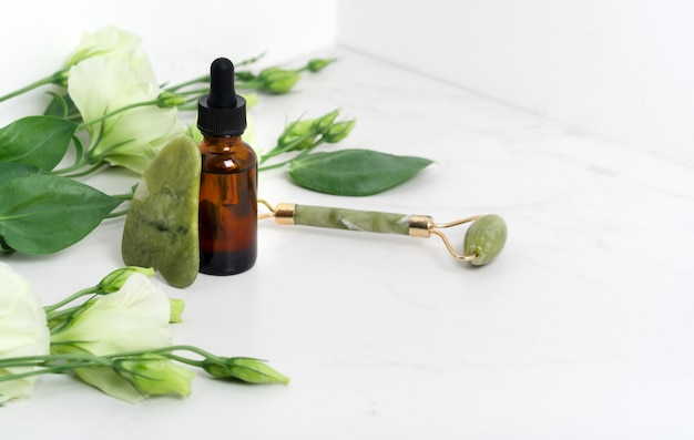 Jaderoller für die gesichtsmassage. grünes gua sha auf dem weißen marmorhintergrund mit flacher lage. anti-aging-behandlung, lifting und toning, akupressur eustoma-blumen. braune serumflasche mit pipette.