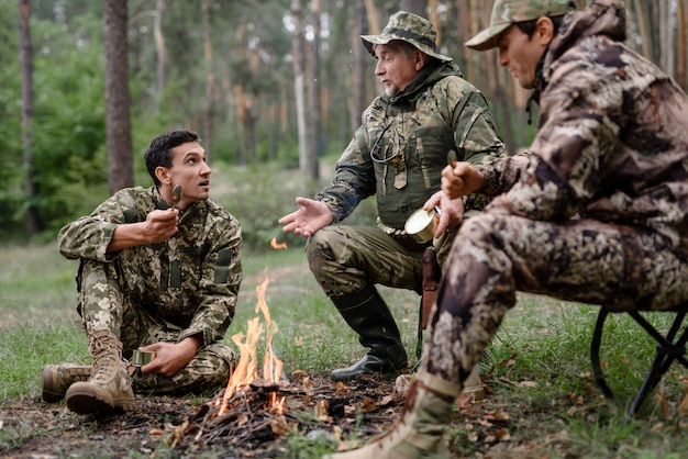 Jäger am lagerfeuer männer haben essen und reden.